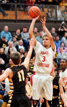 Liberty Christian's Preston Quinn lets go with a jumper from the lane.