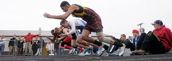 Sprinters shoot out of their starting blocks during a 100-meter dash heat At the Madison County Track and Field Championships on Friday.