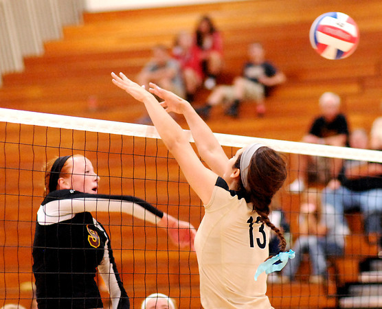 Alexandria's Allie Hueston hits the ball over Madison-Grant's Hunter Wise.