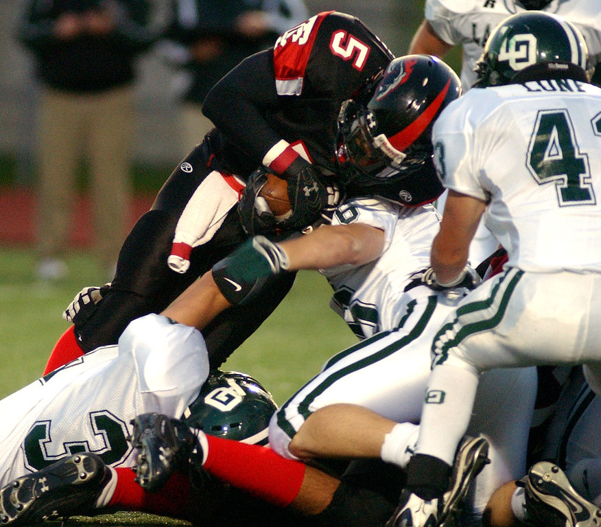 . Troy High School football player Damon Brown, standing left, is tackled by a swarm of Lake Orion defenders during first quarter action, Friday, October 3, 2008, at Troy HS in Troy, Mich.  (The Oakland Press/Jose Juarez)