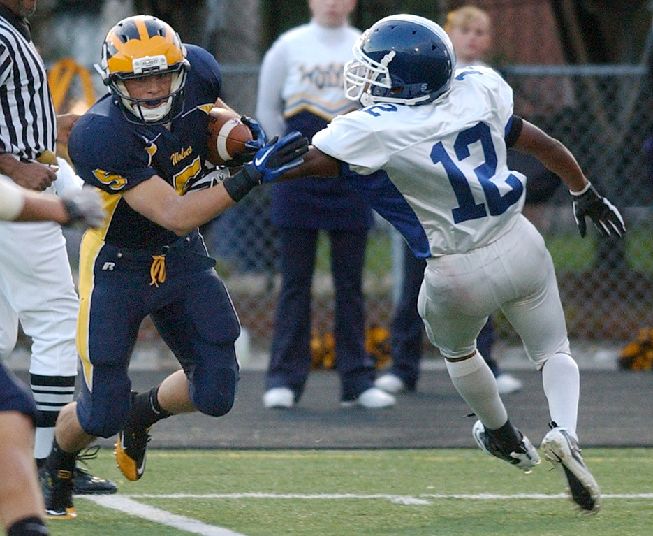 . Clarkston High School football player Joey Goss, left, evades the tackle by Rochester defender T.J. Dean during first quarter action.  Photo taken on Friday, October 1, 2010, in a game played at Clarkston HS in Clarkston, Mich.  (The Oakland Press/Jose Juarez)