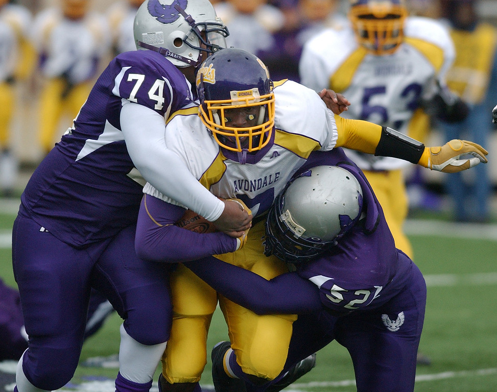 . Auburn Hills Avondale High School football running back D.J. Lynch, middle, runs for yardage as he is tackled by Pontiac defenders Travontay Smith, left, and Keontae Hollis during second quarter action.  Photo taken on Saturday, October 17, 2009, in a game played at Wisner Stadium in Pontiac, Mich.  (The Oakland Press/Jose Juarez)