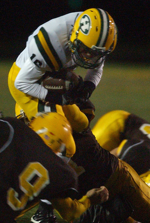 . Farmington Hills Harrison High School football player Aaron Burbridge, top, runs for yardage and is tackled by Rochester Adams defenders during first quarter action, Friday, October 9, 2009, at Adams HS in Rochester Hills, Mich.  (The Oakland Press/Jose Juarez)