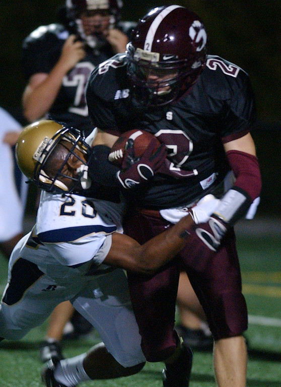 . Birmingham Seaholm High School football player Jasper Apollonia (right, #2) rushes for yardage as he is tackled by Birmingham Detroit Country Day player John Hill (#20) during first quarter action.  Photo taken on Friday, September 16, 2010, in a game played at Birmingham Seaholm HS in Birmingham, Mich.  (The Oakland Press/Jose Juarez)