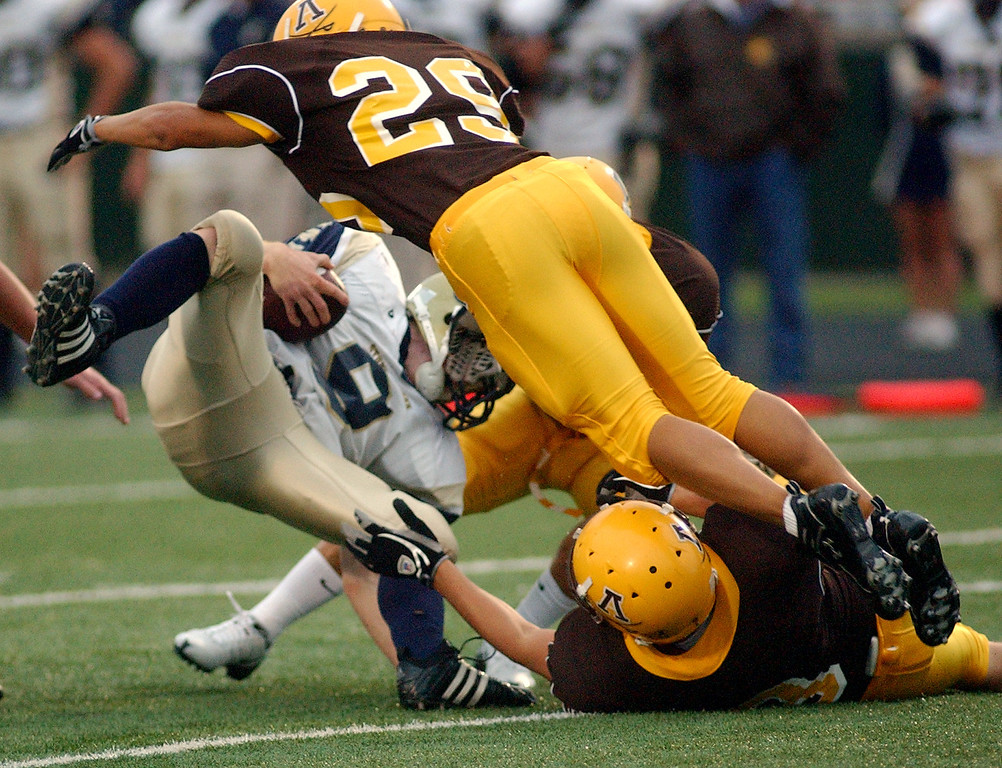 . Stoney Creek High School football running back Danny Cobb (bottom left) is swarmed by several Rochester Adams defenders in the first quarter, Friday, September 5, 2008, in a game played at Adams HS in Rochester Hills, Mich.  (The Oakland Press/Jose Juarez)