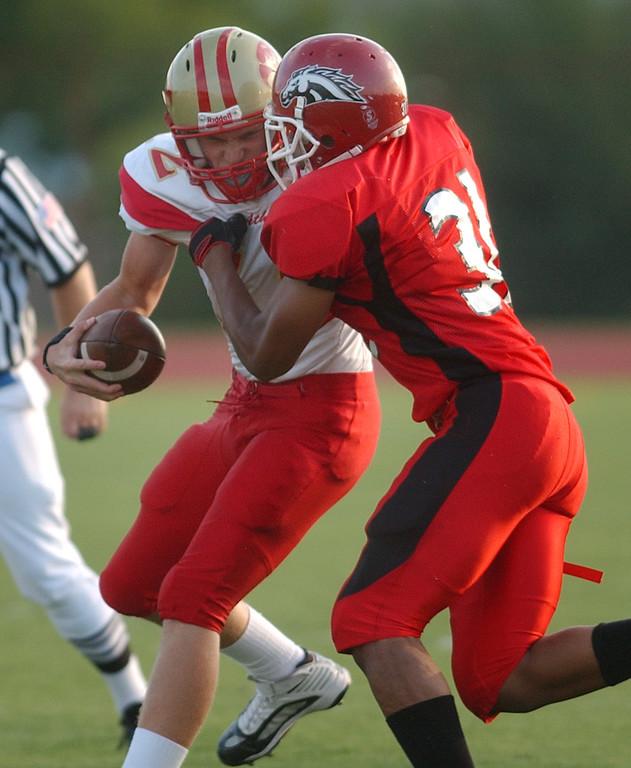. Southfield Lathrup High School football linebacker Tevin Greenwood (right, #31) sacks Troy Athens quarterback Joe Abro (#12) during second quarter action.  Photo taken on Friday, September 11, 2009, at Lathrup High School in Southfield, Mich.  (The Oakland Press/Jose Juarez)