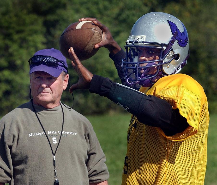 . (left) Pontiac High School football coach Greg Garfield watches QB Jonathon McKnight throw during practice.