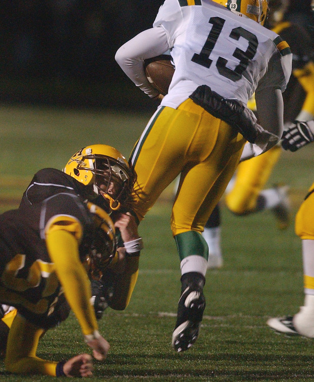 . Farmington Hills Harrison High School football player Cassell Baker, right, runs for yardage and is tackled by a Rochester Adams defender during second quarter action, Friday, October 9, 2009, at Adams HS in Rochester Hills, Mich.  (The Oakland Press/Jose Juarez)