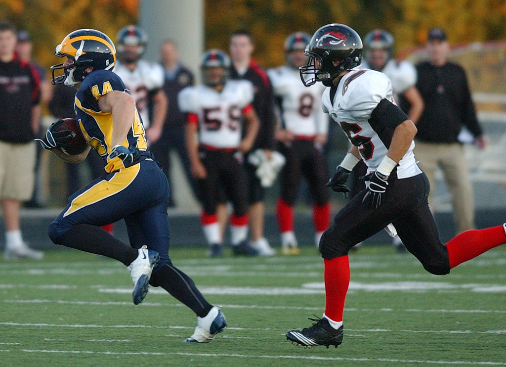 . Clarkston High School football player Evan Montgomery, left, runs for yardage as he is chased by Troy defender Trevor Gilbertson in the first quarter.  Photo taken on Friday, September 17, 2010, in a game played at Clarkston HS in Clarkston, Mich.  (The Oakland Press/Jose Juarez)