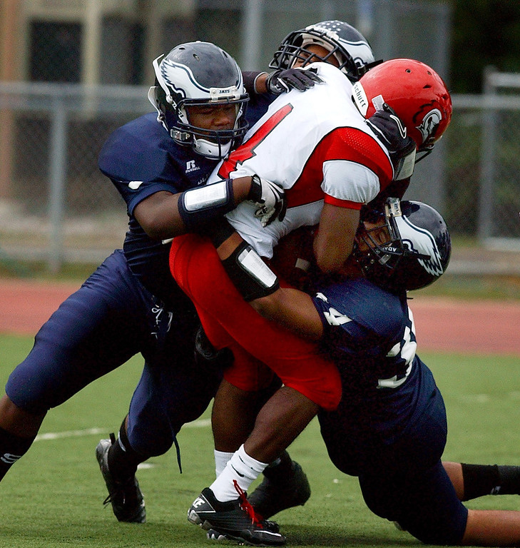 . Several Southfield High School football players swarm Oak Park running back Chris Addison (middle, #4) for no gain on this play during first quarter action.  Photo taken on Friday, September 10, 2010, in a game played at Southfield HS in Southfield, Mich.  (The Oakland Press/Jose Juarez)