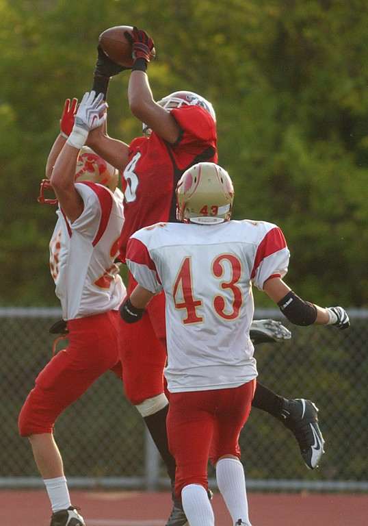 . Southfield Lathrup High School football tight end Austin Long (middle, #8) leaps and hauls in a touchdown pass, past Troy Athens defensive back Daniel Buia (left, #20) and an unidentified Athens defender during second quarter action.  Photo taken on Friday, September 11, 2009, at Lathrup High School in Southfield, Mich.  (The Oakland Press/Jose Juarez)