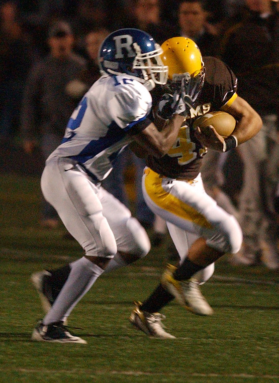 . Rochester Adams High School football player Chris Young (right, #41) runs the ball and is tackled by Rochester defender TJ Dean during first quarter action.  Photo taken on Friday, October 15, 2010, in a game played at Adams HS in Rochester Hills, Mich.  (The Oakland Press/Jose Juarez)