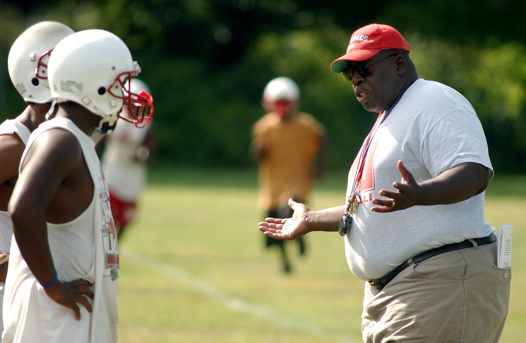 . Pontiac Northern High School football head coach Keith Stephens, far right, chats with two of his players at the start of team practice, Tuesday, August 8, 2006, at Northern HS in Pontiac, Mich.  (The Oakland Press/Jose Juarez)