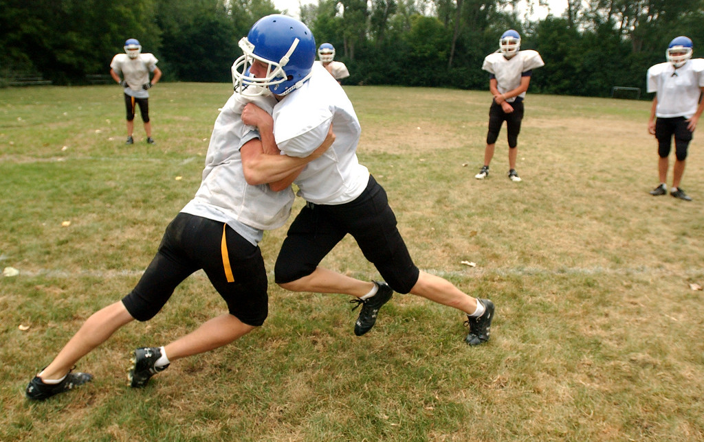 """. Southfield Christian High School football players Justin Basler, left, and Bryan Brownlee work on their tackling skills during a drill called \""""Bull in the Ring.\""""  Photographed during practice held at Southfield Christian HS in Southfield, Mich., Monday, August 14, 2006.  (The Oakland Press/Jose Juarez)"""