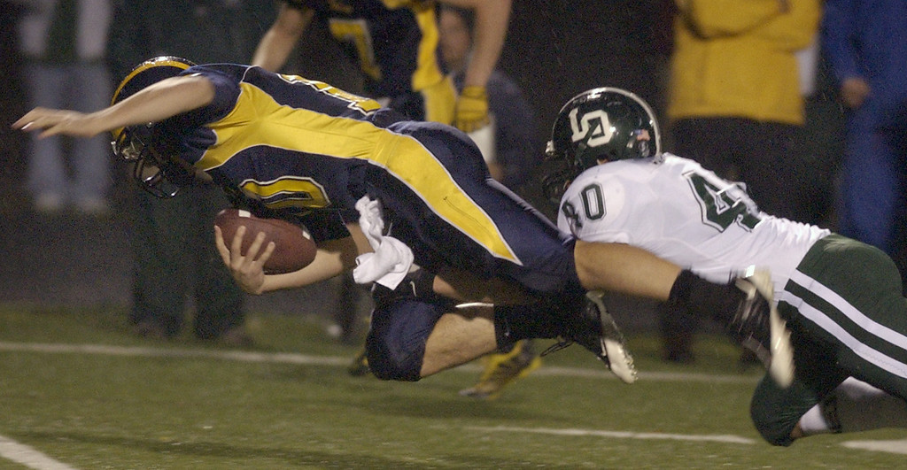 . Clarkston High School football player Tyler Scarlett, left, dives for yardage as he is tackled by Lake Orion defender Nathaniel Quattrochi during first quarter action.  Photo taken on Friday, October 30, 2009, in Clarkston, Mich.  (The Oakland Press/Jose Juarez)