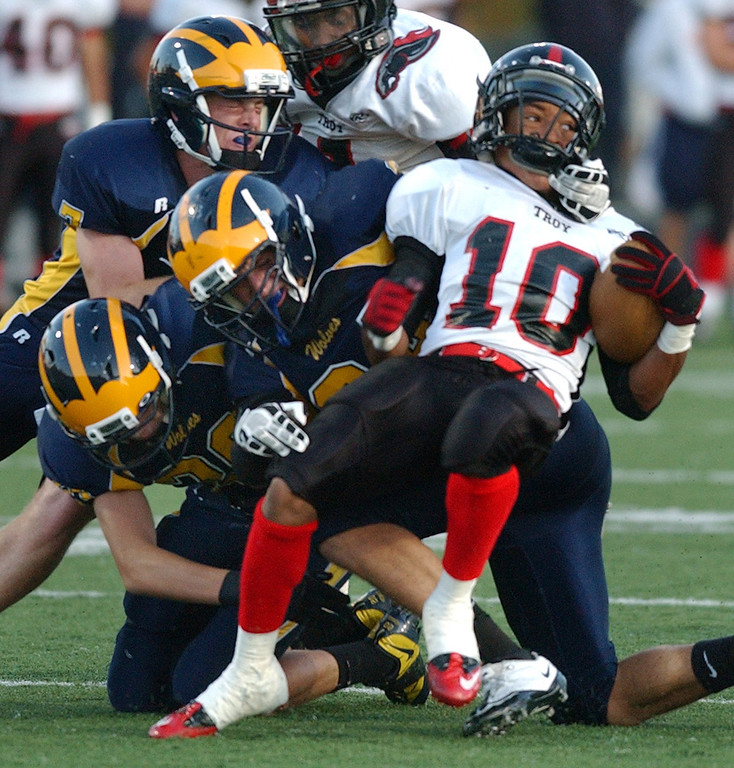 . Troy High School football player James McDonald (right, #10) runs for small yardage as he is tackled by a swarm of Clarkston defenders in the first quarter.  Photo taken on Friday, September 17, 2010, in a game played at Clarkston HS in Clarkston, Mich.  (The Oakland Press/Jose Juarez)