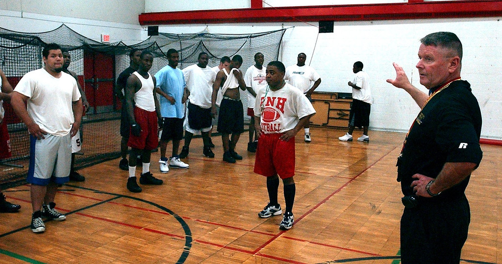. Head coach Gregory Ganfield addresses Pontiac Central and Pontiac Northern High School\'s football players during a break as they work out together for the first time  at Pontiac Northern High School.