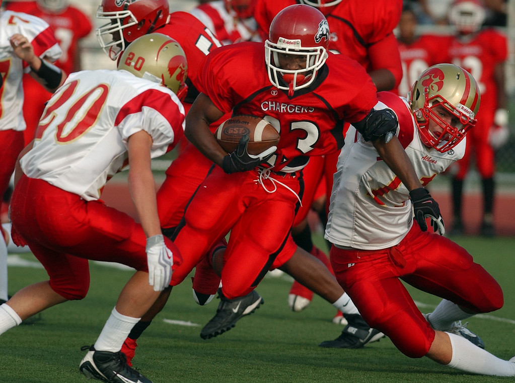 . Southfield Lathrup High School football running back Larry Anthony (middle, #23) runs for yardage and is tackled by Troy Athens defensive back Daniel Buia (left, #20) and Luke Winkle (#11) during first quarter action.  Photo taken on Friday, September 11, 2009, at Lathrup High School in Southfield, Mich.  (The Oakland Press/Jose Juarez)