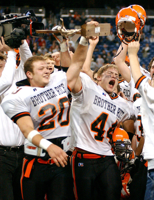 . Birmingham Brother Rice High School football players Mike Radlick (front left, #20) and Matt Pickens (#44) hoist their Division 2 championship trophy after beating Hudsonville, 14-7, Friday, November 25, 2005, at Ford Field in Detroit, Mich.