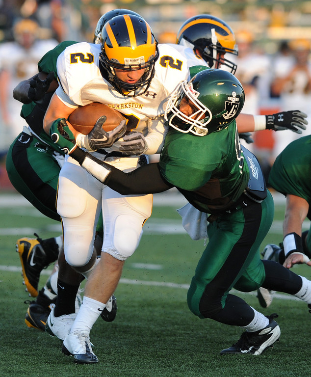. Clarkston High School football player Dakota Bender, left, runs for yardage and is tackled by West Bloomfield cornerback Aaron Foster during first quarter action.  Photo taken on Thursday, September 17, 2009, in a game played at West Bloomfield HS in West Bloomfield, Mich.  (The Oakland Press/Jose Juarez)