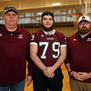Ayer-Shirley senior football player Dante Sequeira, 18, with head coach Phil Marchegiani, left, and his position coach, defensive line coach Shane Brickley, right. Shane is an MIAA honoree for courage after coming back to football from leg surgeries following a skiing injury.  (SUN Julia Malakie)