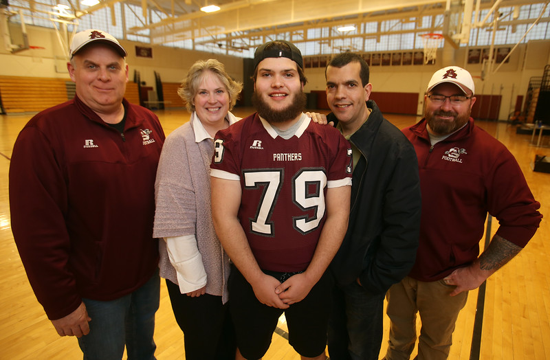 Ayer-Shirley senior football player Dante Sequeira, 18, with head coach Phil Marchegiani, left, his position coach, defensive line coach Shane Brickley, right, and parents Heather and Paul Sequeira. Shane is an MIAA honoree for courage after coming back to football from leg surgeries following a skiing injury.  (SUN Julia Malakie)