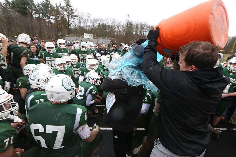 Billerica vs Chelmsford Thanksgiving Day football. Billerica assistant coach Justin Beck pours a bucket of Gatorade over head coach Duane Sigsbury as he talks to players after win. (SUN/Julia Malakie)