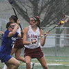 Chelmsford vs Methuen girls lacrosse. Methuen's Hannah McDonald (22) and Chelmsford's Chelsea Cody (18) during second half downpour. (SUN/Julia Malakie)