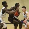 Dracut vs Chelmsford boys basketball. Chelmsford's Suubi Nkugwa (5), center, and Dracut's Farai Zuvaradoka (3) and JC Santiago (24). (SUN/Julia Malakie)
