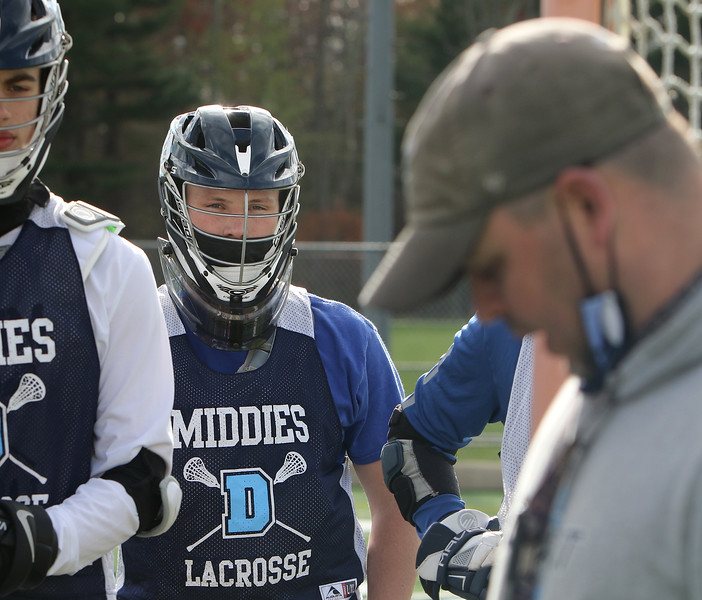 Dracut lacrosse goalie, senior Calvin Desmarais, 18, rear, at practice, as players listen to coach Paul Ganley, right. JULIA MALAKIE/LOWELLSUN