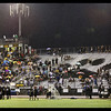 This is the first game of the High School Football 2013 Season. Mesquite High School at Gilbert High School. This is a few minutes before the game started. The rain is falling and teams are making last minute plans. Fans are under umbrellas. The student section ready for the game without umbrellas. The band canceled their performance because of the rain. Referees are discussing the weather and what they will do if lightening gets too close. It's almost game time! <br /> I merged six photographs to get this panorama. I'm always impressed how well Photoshop CS5 stiches them together.