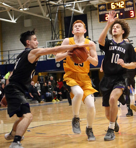 Greater Lowell vs Shawsheen Tech boys basketball. Greater Lowell's Tyler Bussey (33), center, and Shawsheen's Ryan Quinones (11) and Zach Michle (10). (SUN/Julia Malakie)