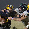 Greater Lowell Tech vs Lowell Catholic football. Greater Lowell's Jacob Trzcienski (4), tackled by Lowell Catholic's Ian Sullivan (75). (SUN/Julia Malakie)