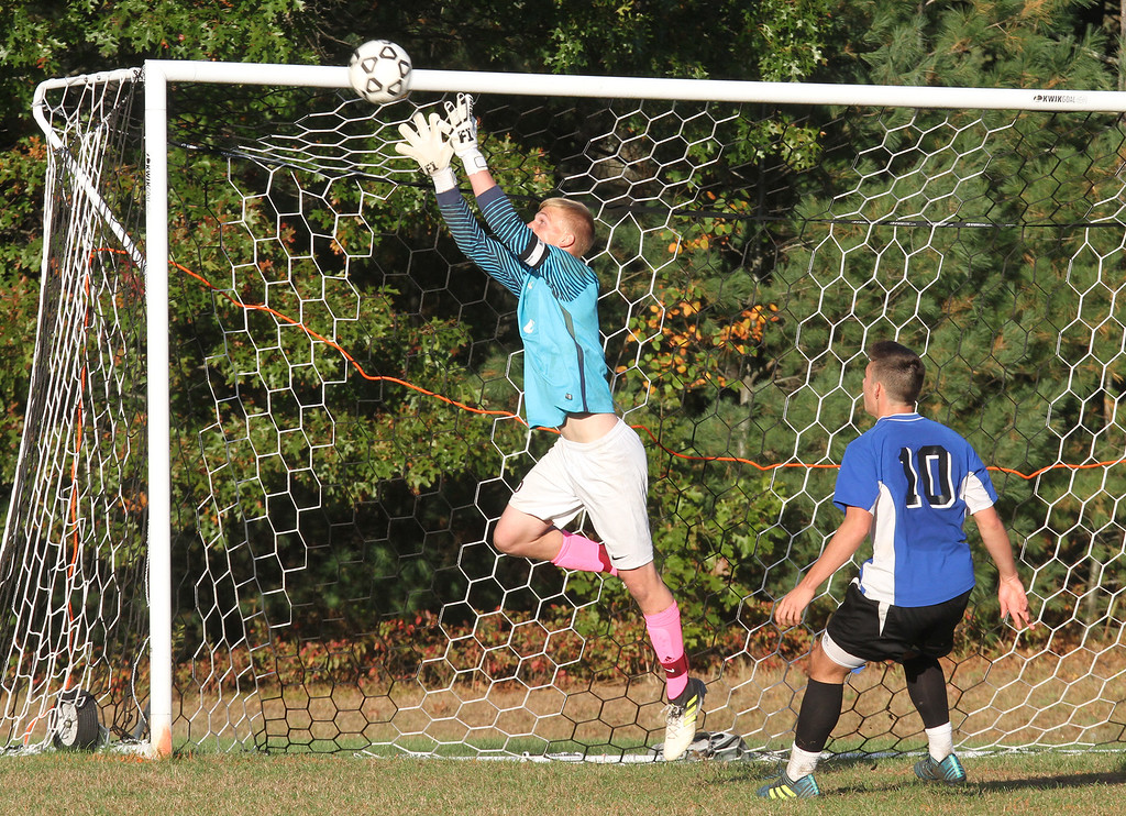 . Groton-Dunstable vs Bromfield Academy boys soccer. Groton-Dunstable goalkeeper Mitchel Hardy stops a shot as Bromfield\'s Charlie Pappas (10) watches.  (SUN/Julia Malakie)