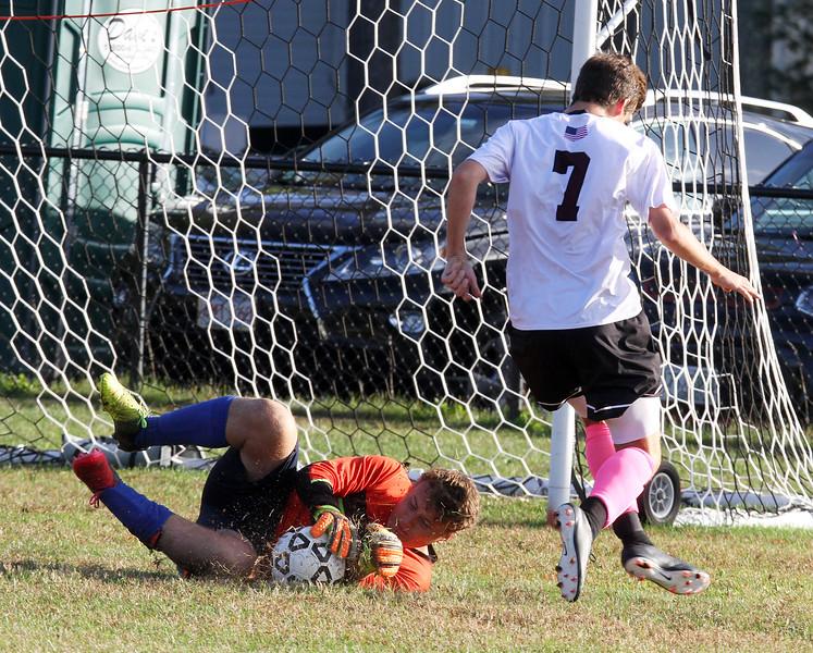 Groton-Dunstable vs Bromfield Academy boys soccer. Bromfield goalkeeper Austin Franklin stops a shot by Groton-Dunstable's Will Zinkann (7). (SUN/Julia Malakie)