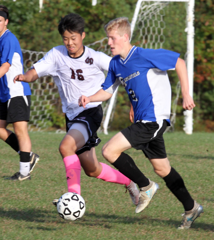 . Groton-Dunstable vs Bromfield Academy boys soccer. Groton-Dunstable\'s Junjae (Peter) Ho (16) and Bromfield\'s Ryell Derjviter (2). (SUN/Julia Malakie)