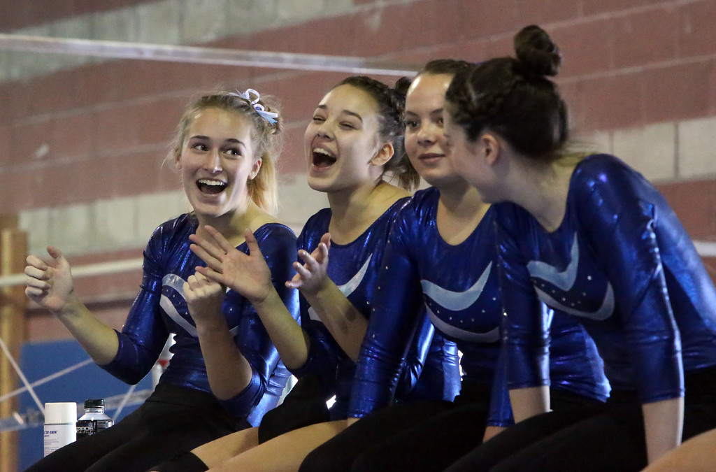 . Chelmsford, Dracut, Billerica and Lowell in gymnastics meet. From left, Sarah Wilson, Mikayla Ganley, Alyssa Quirk and Kate Cournoyer of Dracut cheer for a teammage on the balance beam. (SUN/Julia Malakie)