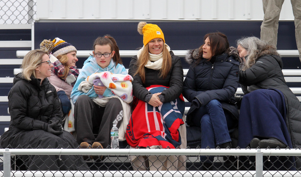 . Littleton girls lacrosse spectators, from left, Dara Furlong, Tracey Johnson, CC Carroll, 13, her mom Lisa Carroll, Carla Archer and Kim McLead, try to stay warm at Alumni Stadium on a cold day for the lacrosse game vs North Middlesex. (SUN/Julia Malakie)