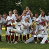Lowell vs Boston Latin softball in MIAA tournament. Lowell players, holding up Nikeishla Yrrizarry (11), center, celebrate win over Boston Latin to advance in MIAA tournament. (SUN/Julia Malakie)