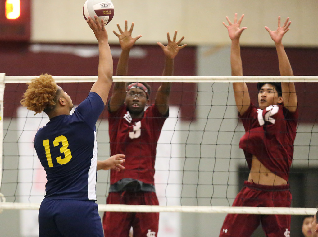 . Lowell vs Greater Lowell boys volleyball, interrupted by leaking roof dripping. Greater Lowell\'s Ajani Phillip (13) and Lowell\'s Eddy Olu (3) and Julien Tang (12). (SUN/Julia Malakie)