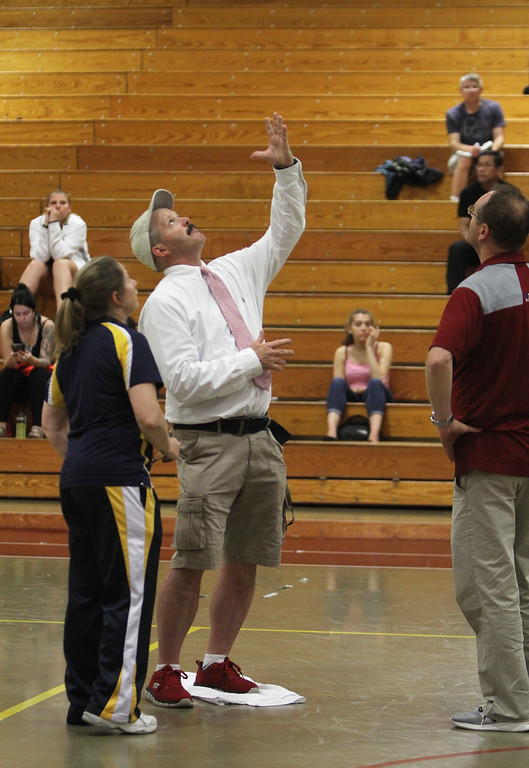 . Lowell vs Greater Lowell boys volleyball, interrupted by leaking roof dripping. From left, Greater Lowell Tech assistant coach Joanne Martin, Lowell head coach Paul McCarthy, with his foot on a towel, and Lowell trainer Kevin Dunham talk about the leak. (SUN/Julia Malakie)