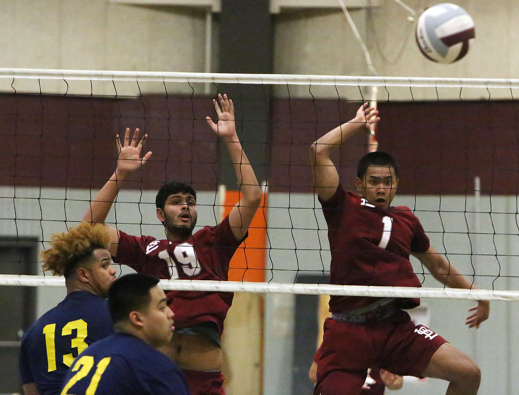 . Lowell vs Greater Lowell boys volleyball. Greater Lowell\'s Ajani Phillip (13) and Meephone Vilavong (21), and Lowell\'s Aakash Patel (19) and Buth Ly (1). (SUN/Julia Malakie)