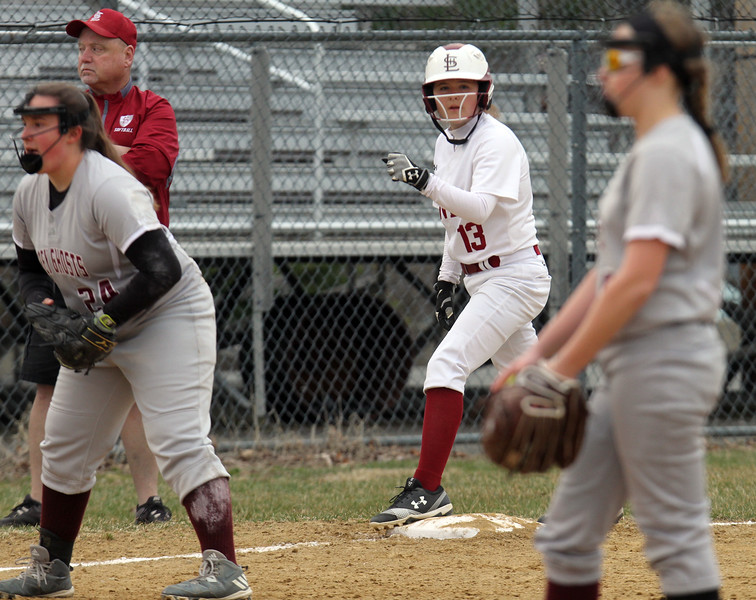 Lowell vs Westford Academy softball. Lowell's Erin McPhee (13) on third base before scoring on a single in the bottom of the third inning. At left, WA third baseman Gigi Ottaviano (24) and at right pitcher Emily Strzegowski (15). (SUN/Julia Malakie)