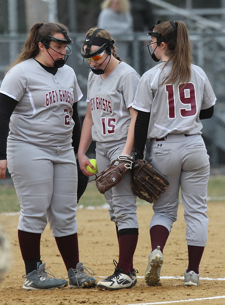 Lowell vs Westford Academy softball. WA third baseman Gigi Ottaviano (24), pitcher Emily Strzegowski (15) and shortstop Maddy Ferreira (19) after Strzegowski caught a line drive for an out in the bottom of the third inning. (SUN/Julia Malakie)