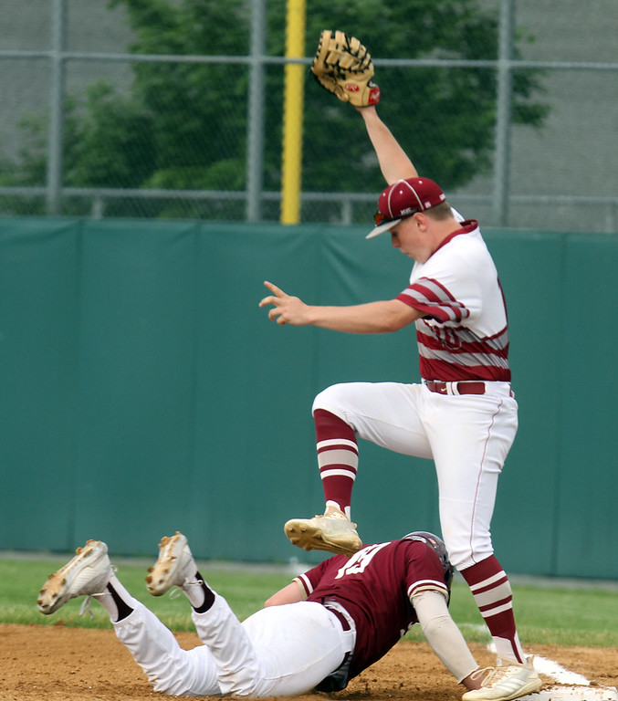 . Lowell vs BC High in MIAA baseball Division 1A tournament. Lowell first baseman Thomas Hassett (10) falls over BC High\'s Pat Roche (19) diving back to first in the top of the first inning. (SUN/Julia Malakie)