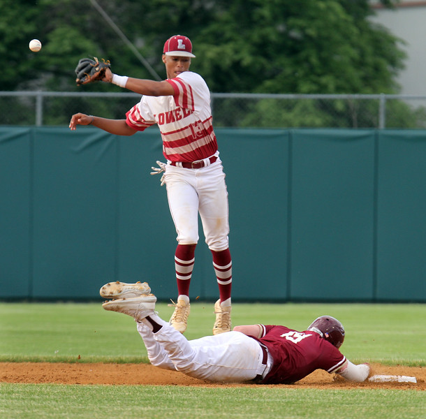 Lowell vs BC High in MIAA baseball Division 1A tournament. BC High baserunner Pat Roche dives back safely to second as Lowell shortstop Raymond Velazquez fields the throw. (SUN/Julia Malakie)