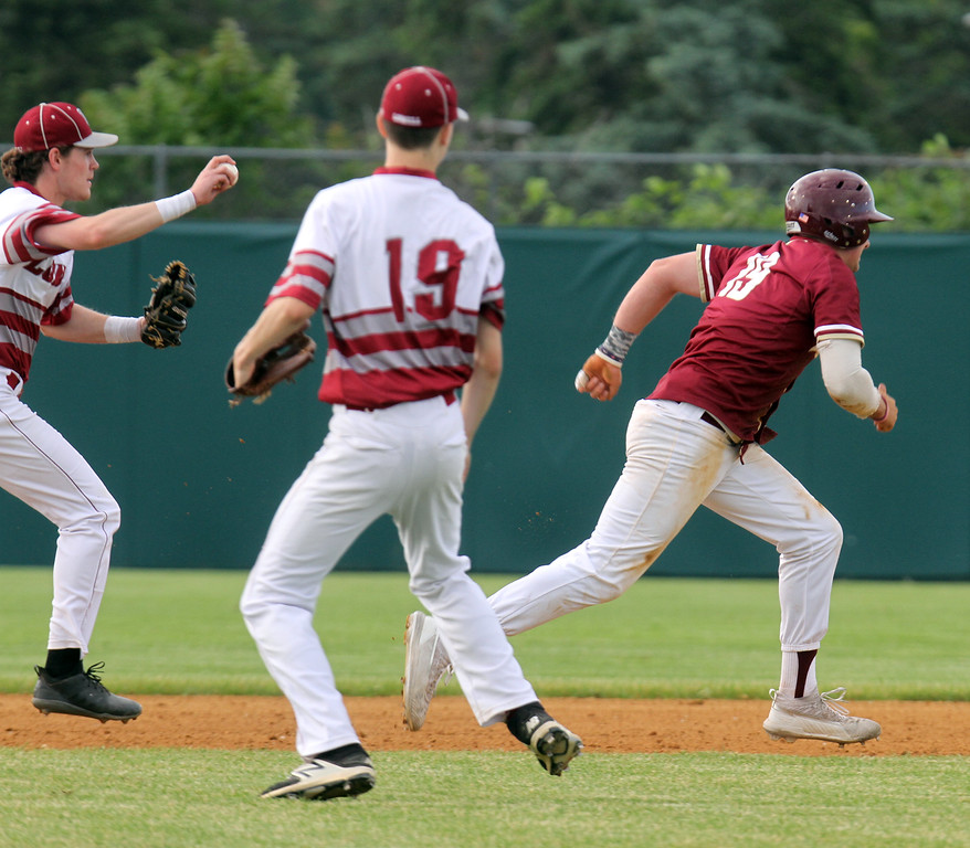 . Lowell vs BC High in MIAA baseball Division 1A tournament. Lowell third baseman Tyler Hoey (7) throws to second and pitcher Timothy Scott (9) watches as BC High\'s Pat Roche (19) is caught in a rundown between second and third in the top of the first inning. (SUN/Julia Malakie)