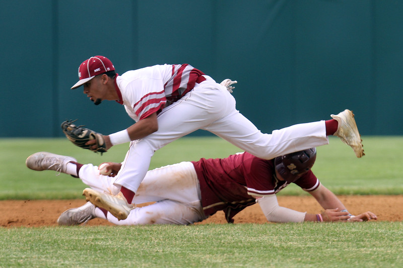 Lowell vs BC High in MIAA baseball Division 1A tournament. Lowell second baseman Jaime Velez (14) tags out BC High's Pat Roche (19) in a rundown between second and third in the top of the first inning. (SUN/Julia Malakie)