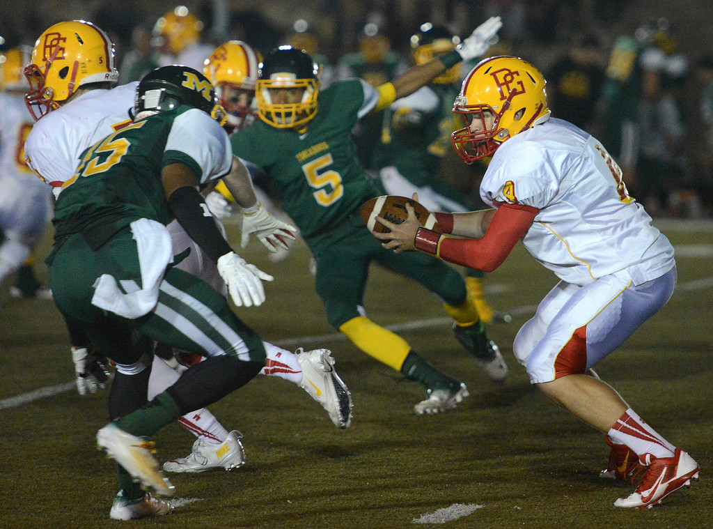 . Pacific Grove\'s quarterback Luke Lowell works under pressure during football in Monterey, Calif. on Friday September 20, 2013.  (Photo David Royal/ Monterey County Herald)