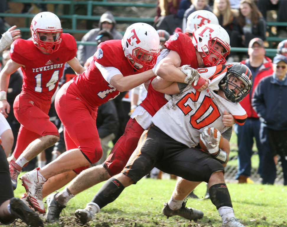 . Tewksbury vs Beverly football in Division 3 semifinal of MIAA state tournament. From left, Tewksbury\'s Derek Graffeo (14), Connor Nugent (77) and Jack Kelly (34), tackling Beverly\'s Andrew Avila (20). (SUN/Julia Malakie)
